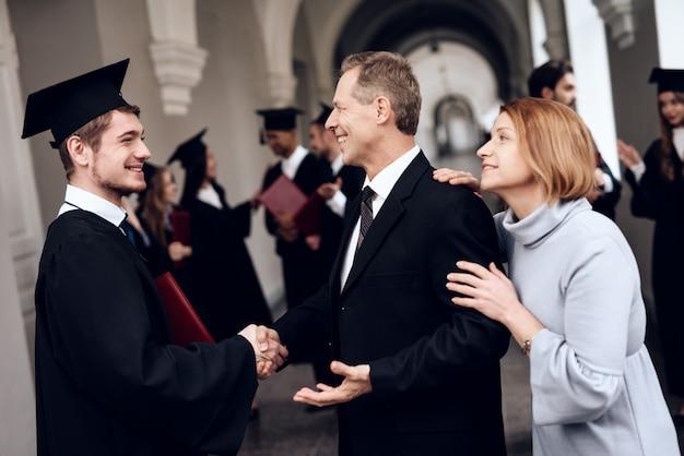 Les parents félicitent l'étudiant qui termine ses études Photo Premium