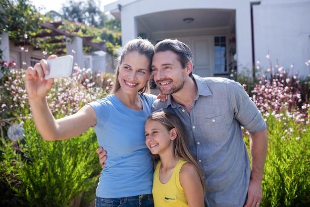 Parents et fille prenant un selfie sur téléphone mobile Photo Premium