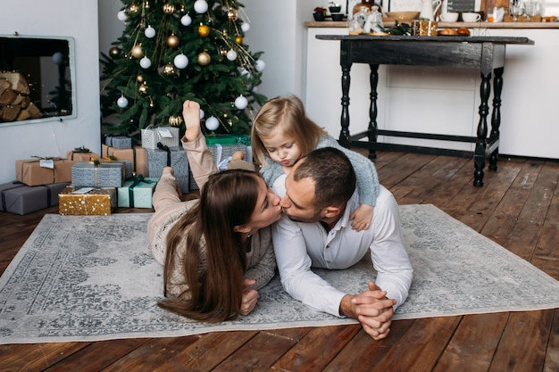 Parents et filles avec des cadeaux à l'étage près de l'arbre de noël à la maison. matin de noël. Photo Premium
