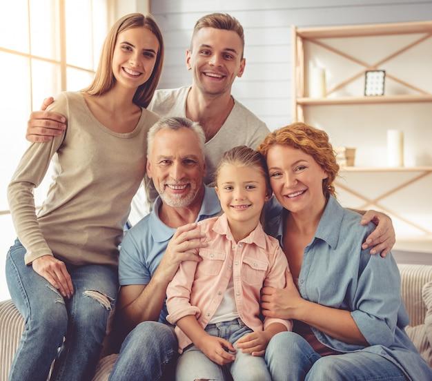 Les parents et les grands-parents s'embrassent, regardant la caméra. Photo Premium