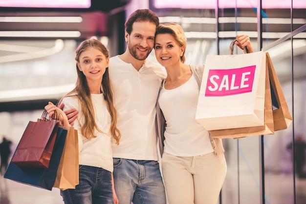 Les Parents Et Leur Fille Tiennent Des Sacs Au Centre Commercial. Photo Premium