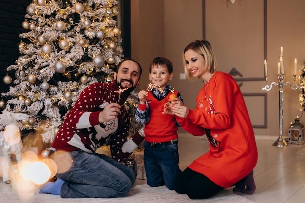 Les Parents Et Leur Petit Fils En Pull Rouge S'amusent Avec Des Oranges Assis Devant Un Sapin De Noël Photo gratuit