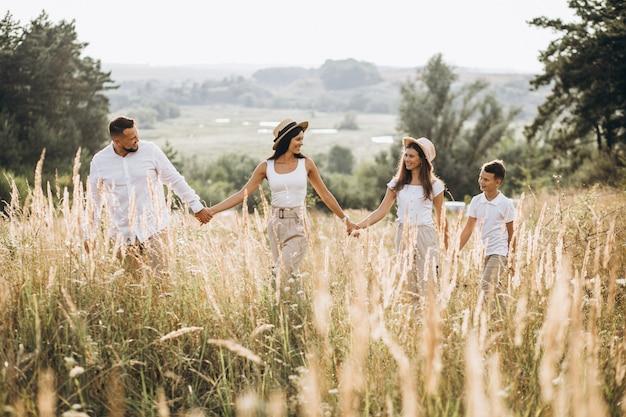 Parents avec leurs enfants marchant dans un champ Photo gratuit