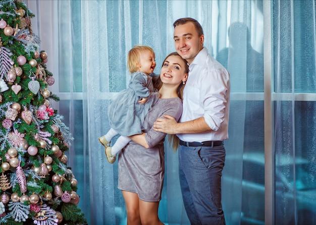 Parents et petite fille attendent noël devant un arbre du nouvel an Photo Premium