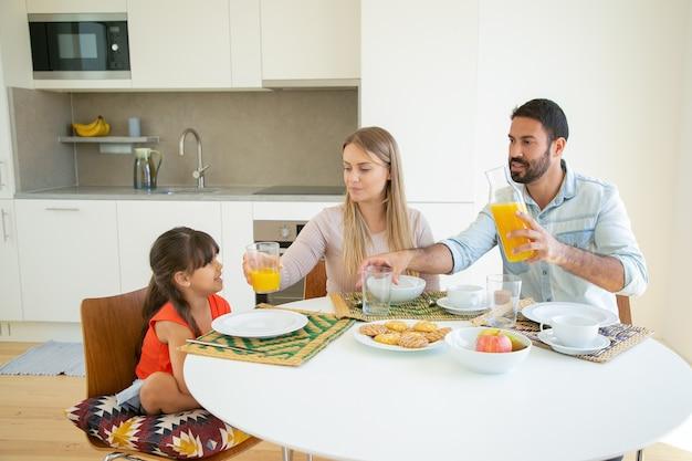 Parents Positifs Et Fille Assise à Table à Manger Avec Plat, Fruits Et Biscuits, Verser Du Jus D'orange. Photo gratuit