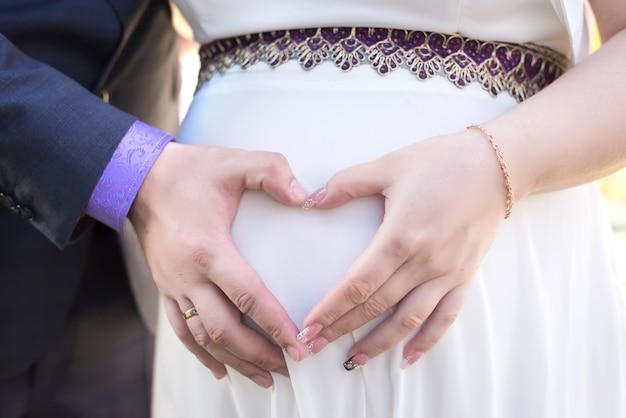 Les parents se tiennent la main sur le ventre Photo Premium