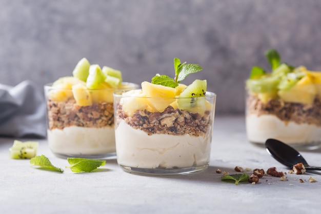 Parfait Au Yogourt Fait Maison Avec Granola, Kiwi, Ananas Et Noix Dans Un Verre Pour Un Petit Déjeuner Sain Sur Fond De Béton Photo Premium