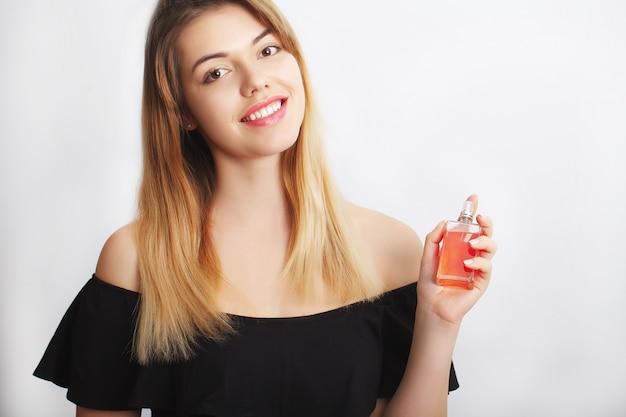 Parfum. jeune jolie femme sentant le parfum avec plaisir Photo Premium
