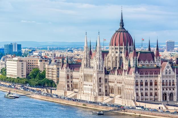 Parlement et rivière à budapest en hongrie avec des bateaux de tourisme pendant la journée d'été avec ciel bleu et nuages Photo Premium