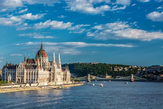 Parlement et rivière à budapest en hongrie avec des bateaux de tourisme pendant la journée d'été ensoleillée avec ciel bleu et nuages Photo Premium