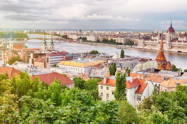 Parlement et rivière à budapest en hongrie pendant la journée d'été ensoleillée avec ciel bleu et nuages Photo Premium