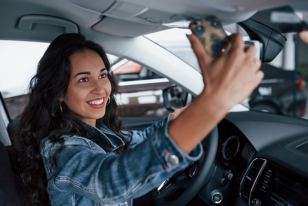 Partager Le Bonheur. Jolie Fille Aux Cheveux Noirs Essayant Sa Toute Nouvelle Voiture Chère Dans Le Salon Automobile Photo gratuit