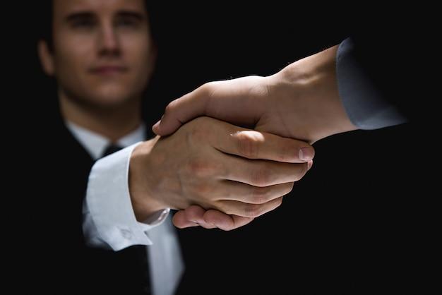 Partenaires commerciaux faisant la poignée de main dans l'ombre Photo Premium