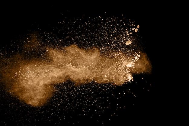 Particules brunes éclaboussées sur fond noir Photo Premium