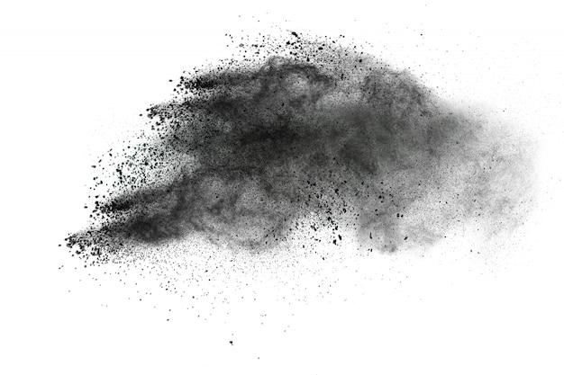 Les particules noires éclaboussent sur fond blanc. la poussière de poudre noire a éclaté. Photo Premium
