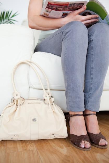 Partie D'une Belle Femme Sur Un Canapé Avec Un Sac Et Un Magazine Photo Premium