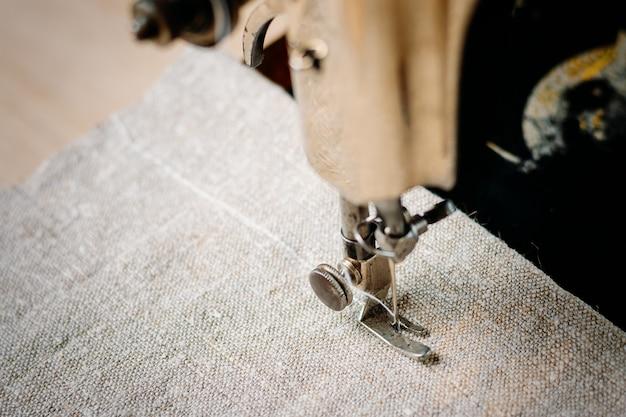 Partie D'une Machine à Coudre Vintage Et D'un Vêtement. Aiguille En Acier Avec Gros Plan Du Boucleur Et Du Pied-de-biche. Photo Premium