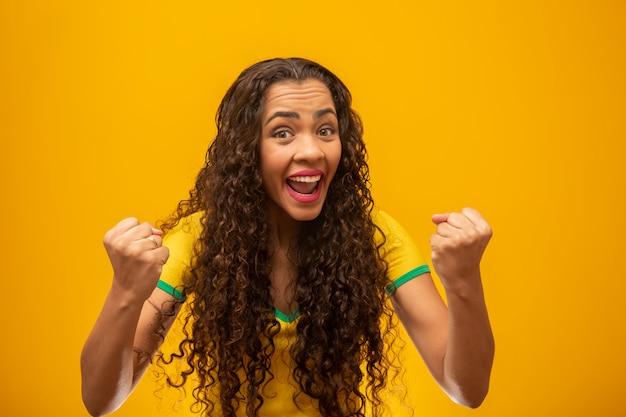 Partisan brésilien de belle jeune femme aux cheveux bouclés. Photo Premium