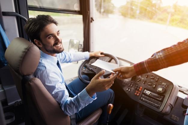 Le passager lui donne un billet pour le trajet en bus Photo Premium