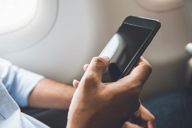 Un passager vient d'éteindre son téléphone portable dans l'avion tout en voyageant pour un vol en toute sécurité Photo Premium