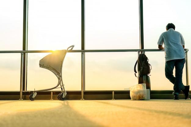 Les Passagers Se Tiennent Près De La Fenêtre Pour Les Avions De Vol Avant Le Départ. Photo Premium