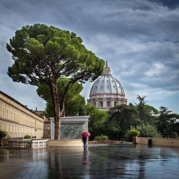Passant Avec Un Parapluie Rouge Marche Par Temps De Pluie Le Long De L'avenue Près De La Cathédrale Saint-pierre Au Vatican. Photo Premium