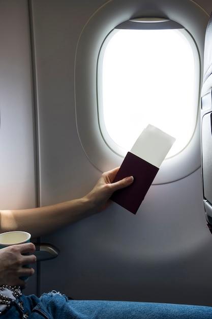 Passeport et billets à côté d'une fenêtre d'avion Photo gratuit