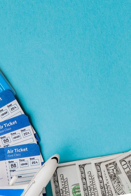 Passeport, dollars, avion et billet d'avion sur un bleu. voyage, copyspace Photo Premium