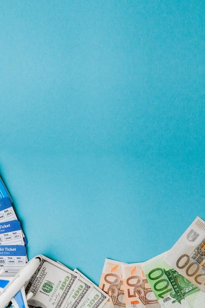 Passeport, dollars et euros, billet d'avion et d'avion sur fond bleu. concept de voyage, espace de copie Photo Premium