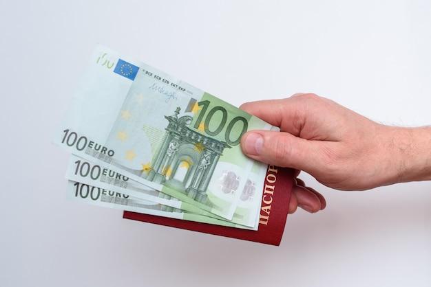 Passeport international russe avec euro dans la main de l'homme Photo Premium