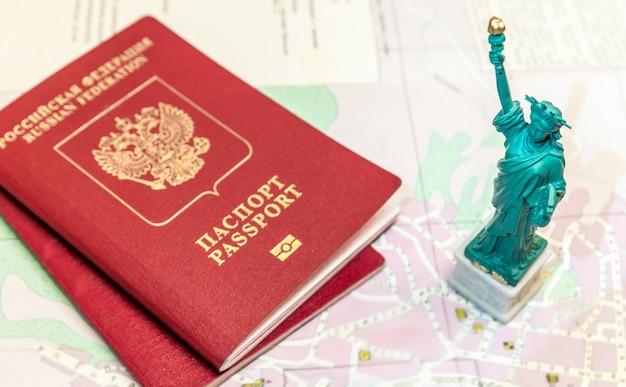 Passeports internationaux russes sur la carte avec la statue de la liberté symbolise le voyage, les vacances Photo Premium