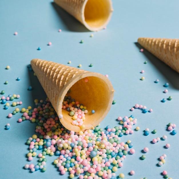Pastel couleur pépites déversant de cône de gaufre sur fond bleu Photo gratuit