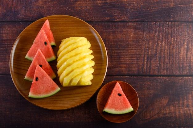 Pastèque Et Ananas Coupés En Morceaux Sur Une Plaque De Bois Photo gratuit