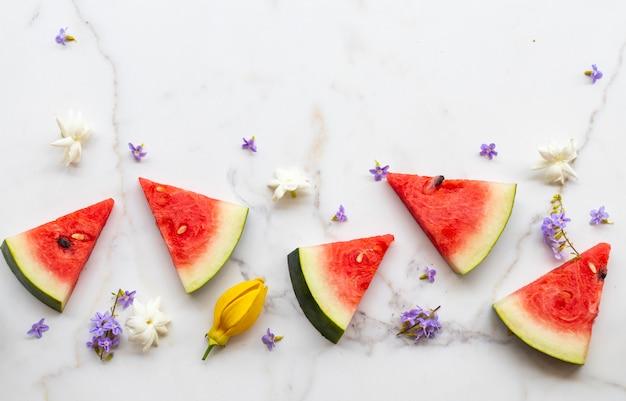Pastèque Coupée Avec Des Fleurs En Arrangement D'été Photo Premium