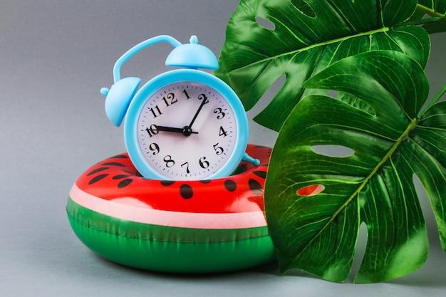 Pastèque Gonflable Sur Fond Gris Avec Des Feuilles De Monstera Et Une Horloge. Concept D'été De Vacances. Photo Premium