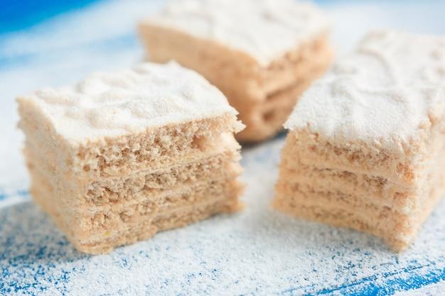 Pastila morceaux sur le fond en bois bleu recouvert de sucre en poudre, vue de côté Photo gratuit