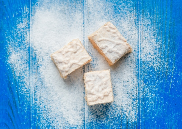 Pastila morceaux sur le fond en bois bleu recouvert de sucre en poudre, vue de dessus Photo gratuit