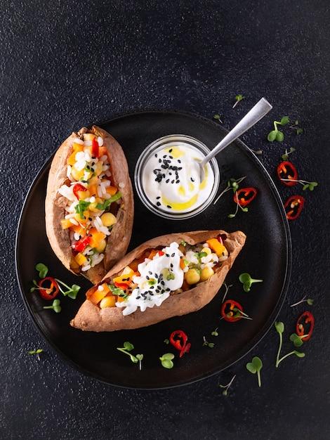 Patate douce ou igname cuite au four, farcie de pois chiches, riz, légumes, vinaigrette au piment rouge et au yogourt Photo Premium