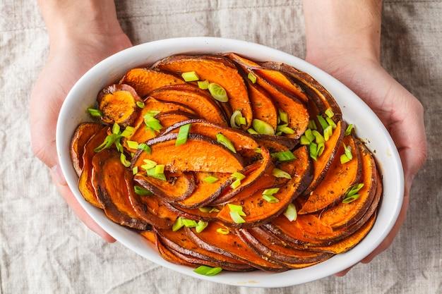 Patate douce tranchée au four avec oignons verts à la main. Photo Premium