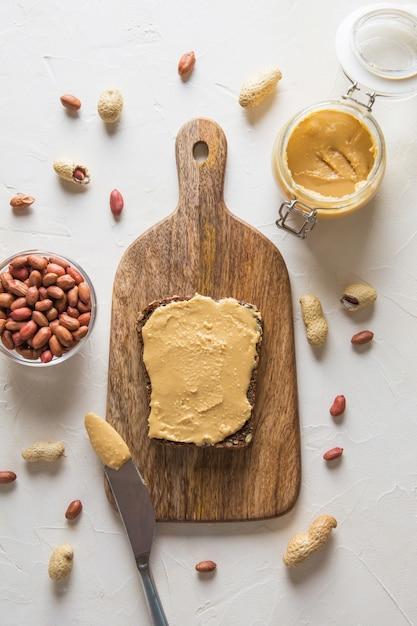 Pâte de cacahuètes sur pain brun complet. alimentation saine. vue d'en-haut. Photo Premium