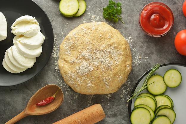 Pâte crue et ingrédients frais pour pizza végétalienne. Photo Premium