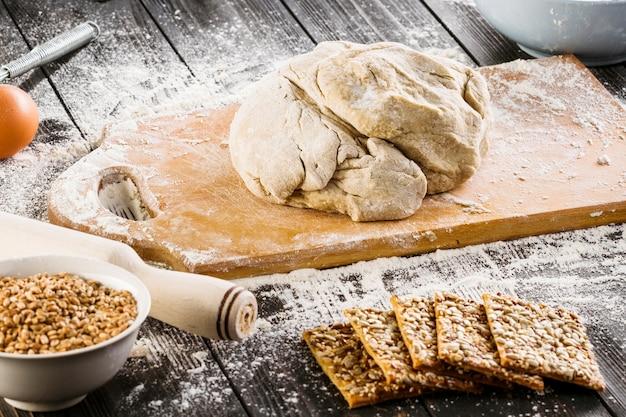 Pâte cuite sur une planche à découper et biscuits sains avec graines de tournesol et graines de lin Photo gratuit
