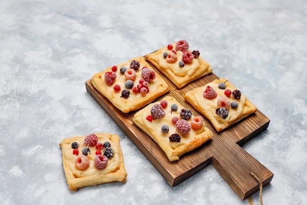 Pâte feuilletée délicieuse fraîche avec des baies sucrées sur du béton Photo gratuit