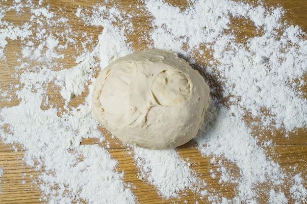 Pâte à levure sur une table en bois saupoudrée. Photo Premium