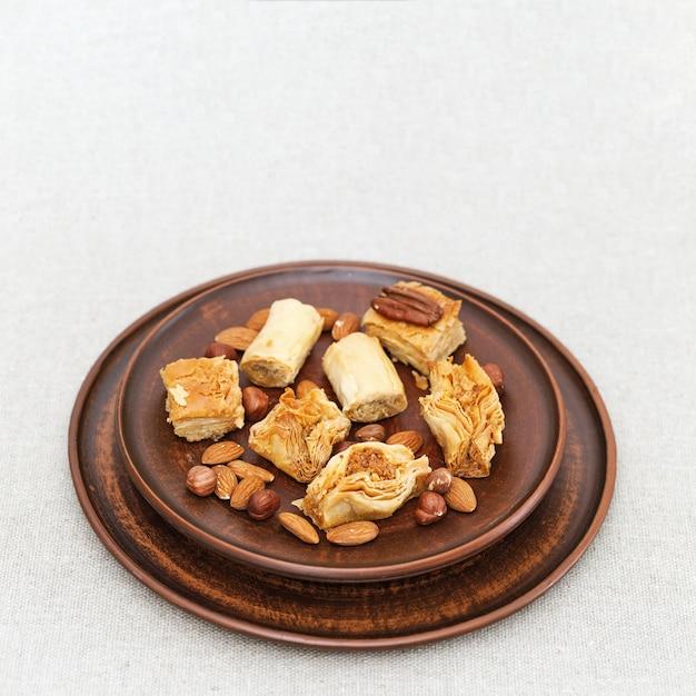 Pâte de pâte phylo (filo) du moyen-orient, noix et miel. plat en terre cuite avec des bonbons Photo Premium