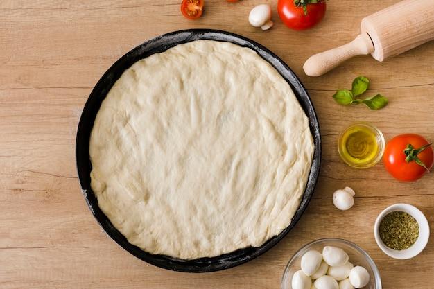 Pâte à pizza non cuite avec garnitures et rouleau à pâtisserie sur un fond en bois Photo gratuit