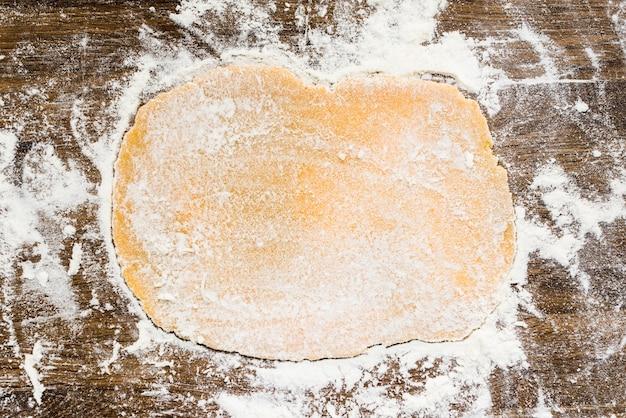 Pâte plate avec de la farine blanche sur une surface en bois Photo gratuit