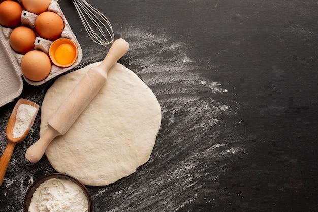Pâte avec rouleau à pâtisserie et carton d'oeufs Photo gratuit