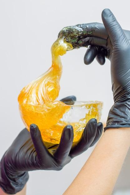Pâte de sucre ou miel de cire à épiler avec des gants noirs, mains du cosmétologue au salon spa Photo Premium