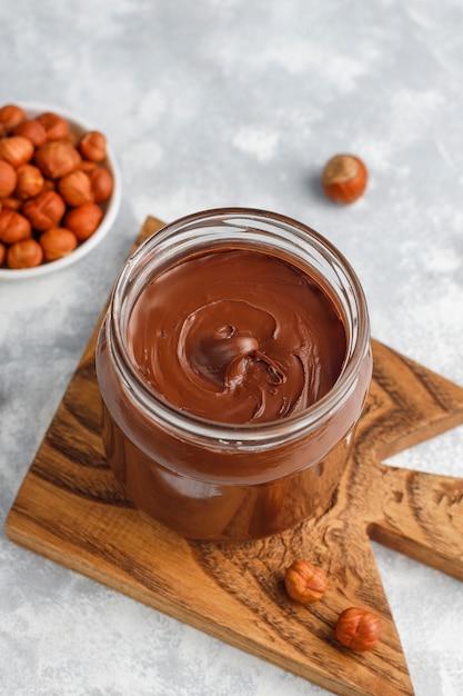 Pâte à Tartiner Au Chocolat Ou Crème De Nougat Aux Noisettes Dans Un Bocal En Verre Sur Du Béton, Fond Photo gratuit